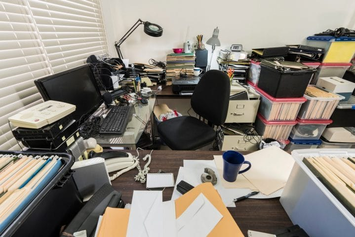 Messy business office with piles of files and disorganized clutt